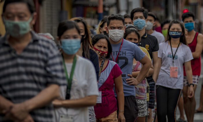 Customers wearing facemasks queue outside a grocery in Manila, Philippines, on April 23, 2020. (Ezra Acayan/Getty Images)