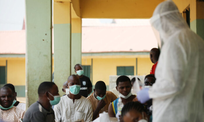 People wait as health workers prepare to take samples during a community CCP virus testing campaign in Abuja, Nigeria, on April 15, 2020. (Kola Sulaimon/AFP via Getty Images)