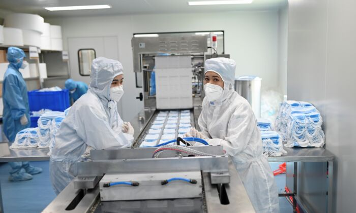 Two workers prepare to package masks at Naton Medical Group in Beijing, China on April 24, 2020. (WANG ZHAO/AFP via Getty Images)