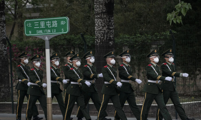 Chinese police wear protective masks as they march during a shift change on April 14, 2020 in Beijing, China. Monitoring and enforcement of virus-related measures and the quarantine of anyone arriving to Beijing is carried out by neighborhood committees and a network of Communist Party volunteers who wear red arm bands.  (Kevin Frayer/Getty Images)