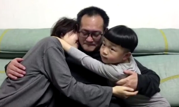 Wang Quanzhang embraces his wife and son at their home in Beijing, on April 27, 2020. (Screenshot via Reuters)