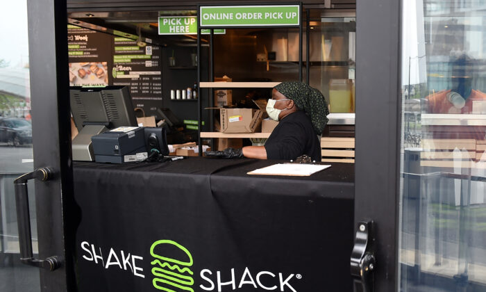 A Shake Shack employee wears a masks as she prepares food orders for pickup during the Coronavirus pandemic in Arlington, Virginia, on April 20, 2020. (OLIVIER DOULIERY/AFP via Getty Images)