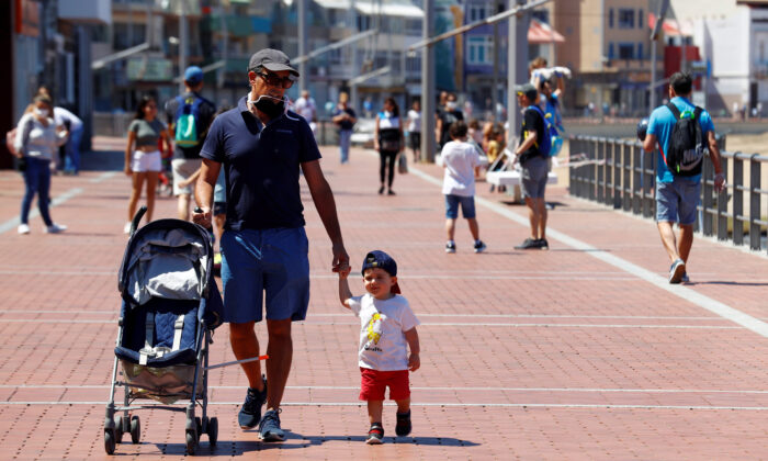 Children walk with their parents at promenade of Las Canteras beach after restrictions were partially lifted for children for the first time in six weeks, following the CCP virus (COVID-19) outbreak on the island of Gran Canaria, Spain, on April 26, 2020. (Borja Suarez/Reuters)
