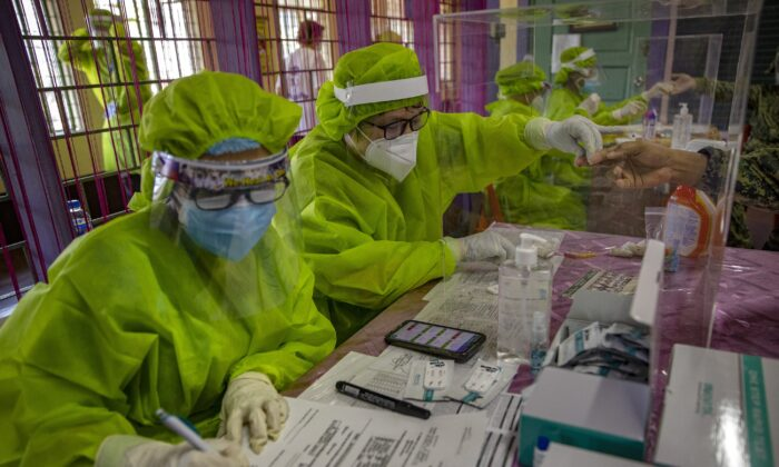Medical personnel test people for COVID-19 using rapid antibody testing kits, at a school converted into a mass testing facility, in Manila, Philippines on April 24, 2020. (Ezra Acayan/Getty Images)