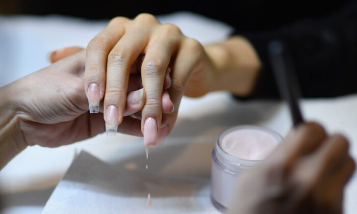 """Colombian Beauty Vlogger Paula Galindo gets her nails done by nail artist and entrepreneur Jenny Bui aka """"The Queen of Bling"""" in her nail salon in the Bronx Borough of New York City on Jan. 10, 2020.(Angela Weiss/AFP via Getty Images)"""