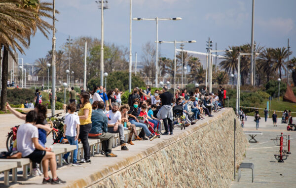 Families with their children sit in a boulevard