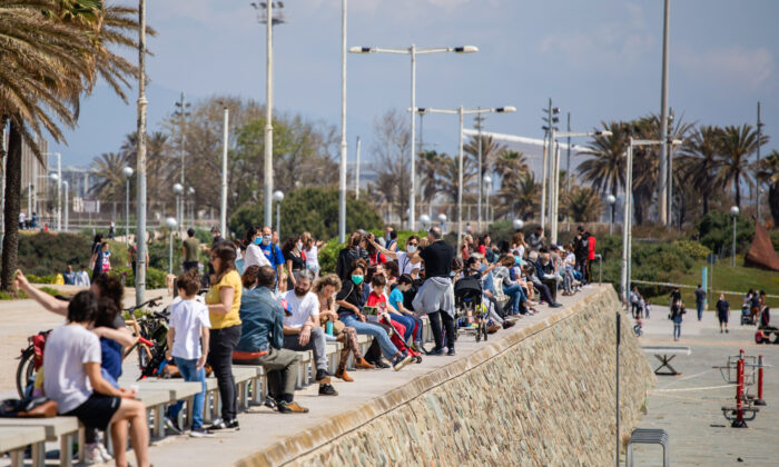 Families with their children sit in a boulevard as police patrol the beach, where access is prohibited, in Barcelona, Spain on April 26, 2020. (Emilio Morenatti/AP)