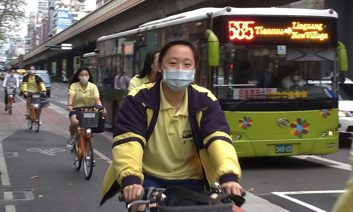 Students wear protective face masks as they ride on a street in Taipei, Taiwan, on April 21, 2020. Taiwan used location-tracking capabilities in smartphones to great effectiveness during the pandemic. (AP Photo/Chiang Ying-ying)