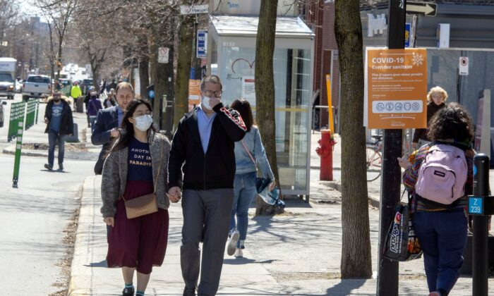 Pedestrians wearing protective masks walk along a sidewalk in Montreal on April 28, 2020. (The Canadian Press/Ryan Remiorz)