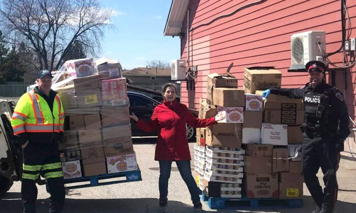 Storehouse Food Bank coordinator Laura Bogner (C) with donations delivered to the food bank by the Durham Regional Police Service and partners, in Ajax, Ont., on April 22, 2020. (Courtesy of Laura Bogner)