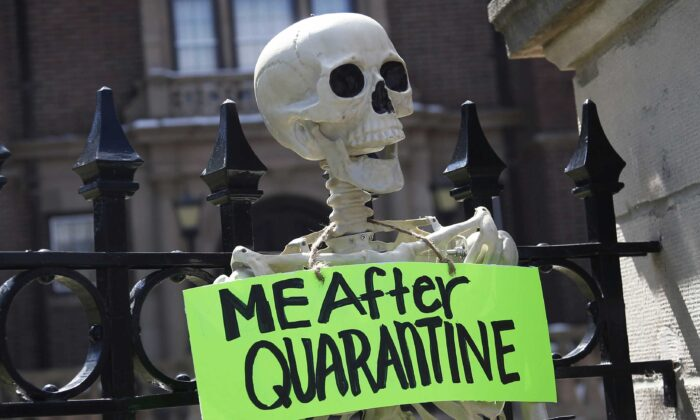 A mock skeleton is attached to the fence as protesters gathered outside Minnesota Gov. Tim Walz' official residence in St. Paul, Minn., on April 17, 2020, to call on him to loosen stay-at-home restrictions imposed across the state because of the coronavirus. (Jim Mone/AP Photo)