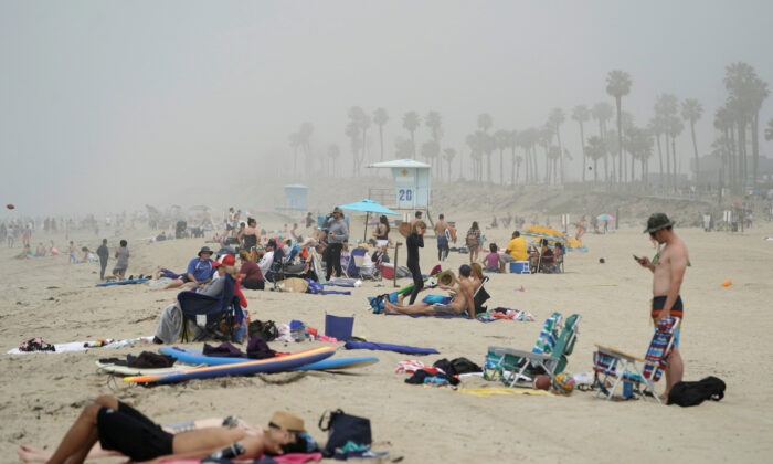 People sit in groups at Huntington City Beach during the outbreak of the CCP virus (COVID-19) in Huntington Beach, Calif., on April 25, 2020. (Kyle Grillot/Reuters)