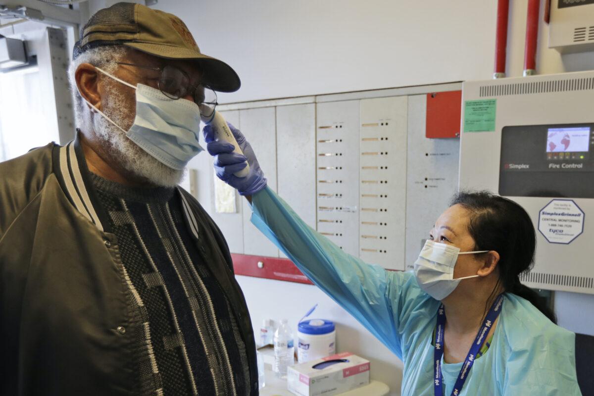 Registered Nurse Janice Tatonetti (R) takes the temperature
