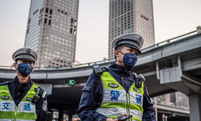 Police officers wearing facemasks patrol on a street in Beijing on April 7, 2020. (Nicolas Asfouri/AFP via Getty Images)