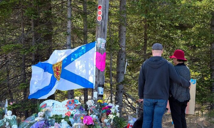 A couple pays their respects at a roadblock in Portapique, Nova Scotia, Canada, on April 22, 2020. (Andrew Vaughan/The Canadian press)
