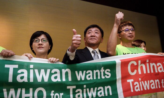 Taiwan's health Minister Chen Shih-chung (C) gives a thumb up as he poses with demonstrators after a press conference on the sideline of the World Health Organization annual Assembly in Geneva, Switzerland, on May 21, 2018. (Fabrice Coffrini /AFP via Getty Images)