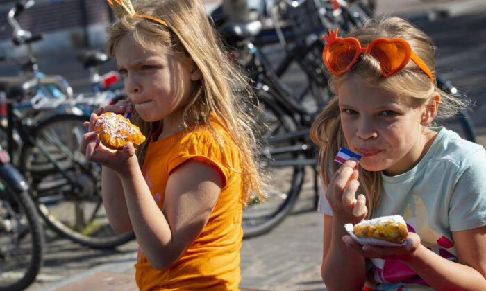 Two girls enjoy traditional King's Day pastry in Amsterdam, Netherlands, Monday, April 27, 2020. The Dutch national birthday party was a muted affair, dubbed King's Day at Home because of coronavirus restrictions, a far cry from the usual nationwide celebration with street parties. (Peter Dejong/AP)
