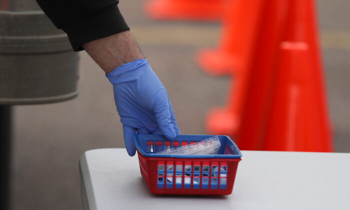 A drive-through customer picks up a swab kit at a Rite Aid drive-through testing site in Macomb, Michigan, on April 21, 2020. (Gregory Shamus/Getty Images)