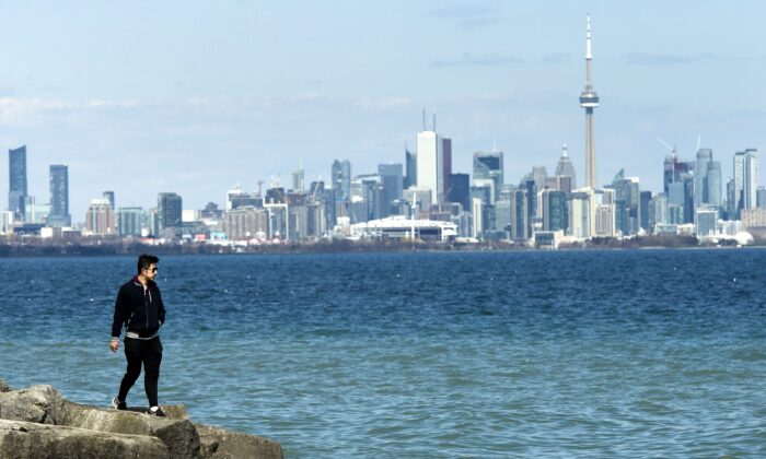 A man walks on the shore of Lake Ontario with the Toronto skyline in the background on April 27, 2020. Provincial governments are beginning to announce plans to progressively reopen businesses and the economy. (The Canadian Press/Nathan Denette)