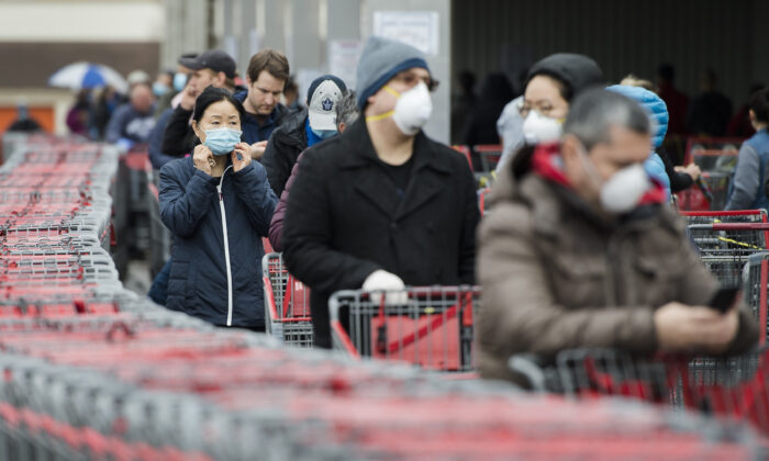Hundreds of people wait in line to enter Costco in Toronto on April 13, 2020. The way people shop in stores has changed for the foreseeable future given the need and desire for physical distancing. (The Canadian Press/Nathan Denette)