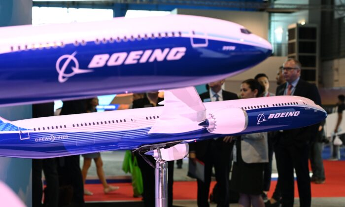 Visitors look at Boeing 787 and 777 model displays at the Singapore Airshow in Singapore, on Feb. 12, 2020. (Roslan Rahman/AFP via Getty Images)
