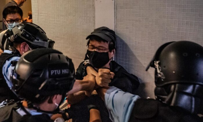 Police detain a man during the sing with you rally outside a shopping mall in Hong Kong on April 26, 2020. (Anthony Kwan/Getty Images)