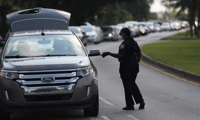 A City of Opa-locka police officer directs a line of cars to the drive-thru Feeding South Florida food distribution site in Opa-locka, Fla., on April 14, 2020. Feeding South Florida has seen a 600 percent increase in those asking for food aid as people, some of whom have lost jobs, need to make ends meet during the coronavirus pandemic. (Joe Raedle/Getty Images)