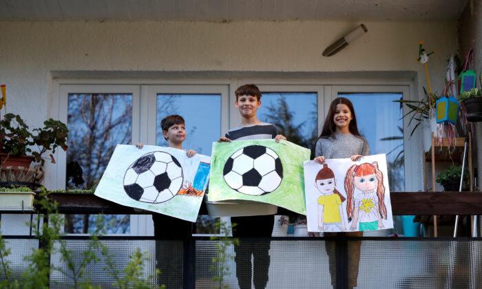 Ivan Posta, 8, Vince Posta, 11, and Vilma Posta in Budapest, Hungary, on April 10, 2020. (REUTERS/Bernadett Szabo)