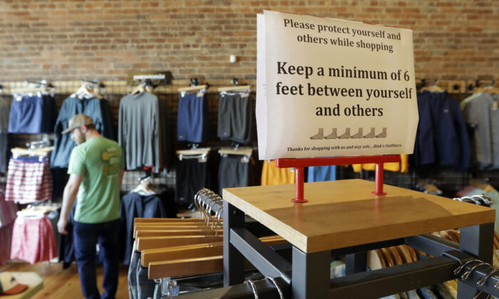A sign reminding customers of social distancing is posted in the Bink's Outfitters store in Murfreesboro, Tenn., April 29, 2020. (Mark Humphrey/AP Photo)