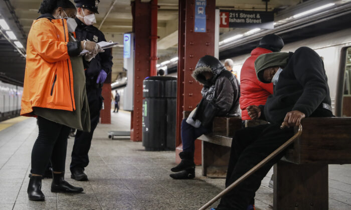 Homeless outreach personnel assist passengers found sleeping on subway cars at the 207th Street A-train station, in the Manhattan borough of New York, Thursday, April 30, 2020. (John Minchillo/AP Photo)