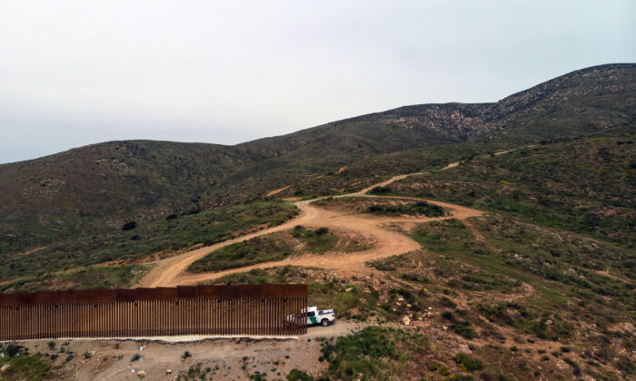 A Border Patrol vehicle is parked next to a section of the U.S.–Mexico border fence as it ends at El Nido de las Aguilas, Baja California, on March 26, 2019. (Guillermo Arias/AFP via Getty Images)