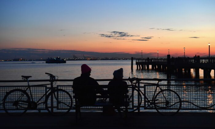 A couple watches the sunset amid the novel coronavirus pandemic in New York City on April 28, 2020. New York, which has ground to a halt to stop the coronavirus pandemic, may start reopening manufacturing and construction after May 15, Governor Andrew Cuomo said on April 26. (Angela Weiss/AFP via Getty Images)