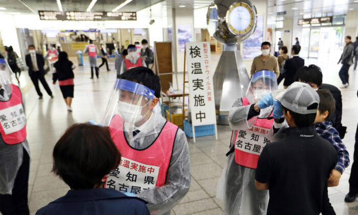 Staff members of Aichi Prefecture, wearing protective gear as a preventive measure to curb the spread of the CCP virus, check the body temperature of passengers arriving at Nagoya railway station, Japan, on April 29, 2020. (STR /Jiji Press/ AFP via Getty Images)