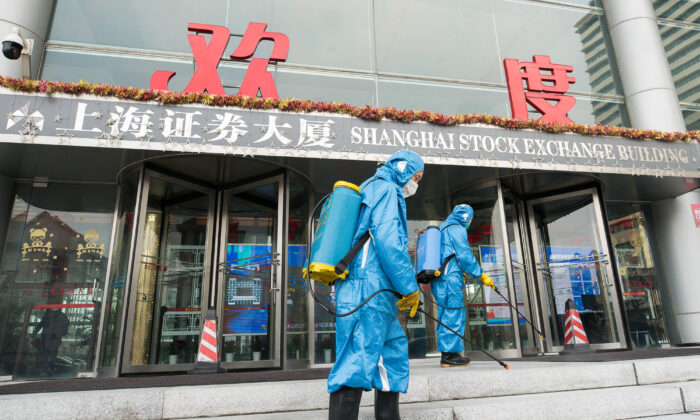 Medical workers spray antiseptic outside of the main gate of Shanghai Stock Exchange Building in Shanghai on Feb. 03, 2020.       (Yifan Ding/Getty Images)