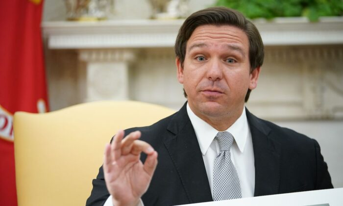 Florida Governor Ron DeSantis holds up a photo during a meeting with U.S. President Donald Trump in the Oval Office of the White House in Washington, on April 28, 2020. (Mandel Ngan/AFP via Getty Images)