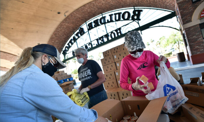 Volunteers prepare groceries to be given out at a drive-thru Three Square Food Bank emergency food distribution site at Boulder Station Hotel & Casino in response to an increase in demand amid the COVID-19 pandemic in Las Vegas, Nev. on April 29, 2020. (David Becker/AFP/Getty Images)