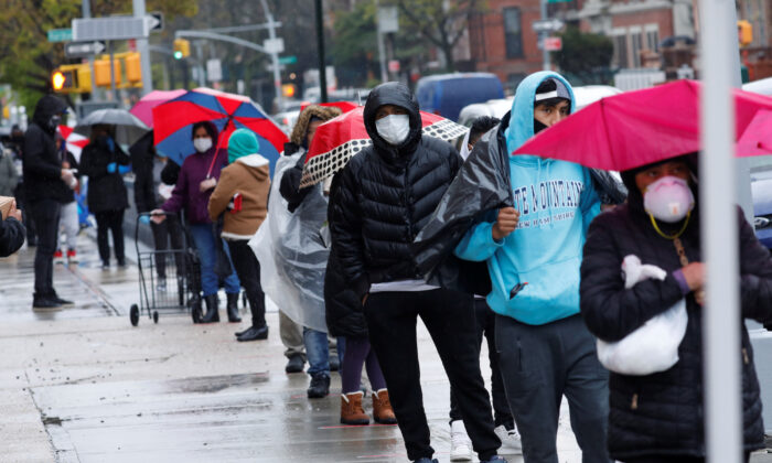 People wearing protective face masks wait in line to receive free food at a curbside pantry for needy residents in New York City, New York, on April 24, 2020. (Reuters/Mike Segar)