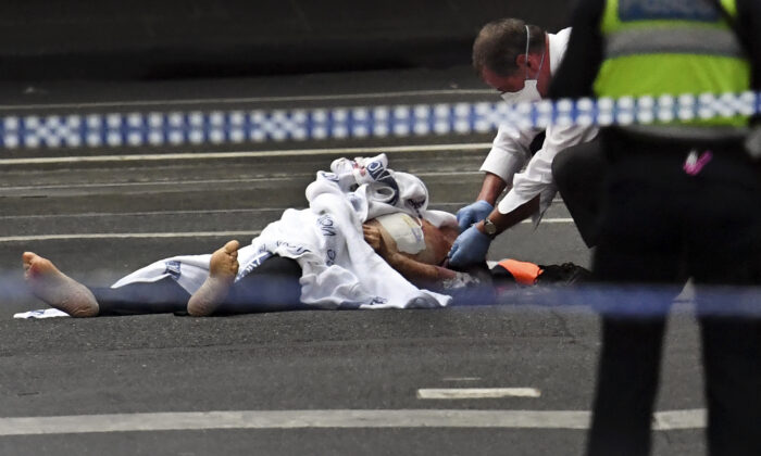 A police officer inspects a body at the crime scene following a stabbing incident in Melbourne on November 9, 2018. (William WEST / AFP)