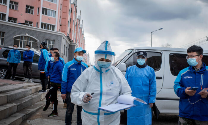 A medical worker checks notes in front of food delivery employees, who wait in line to have their nucleic acid test, at a health services center in Suifenhe, China on April 24, 2020. (STR/AFP via Getty Images)