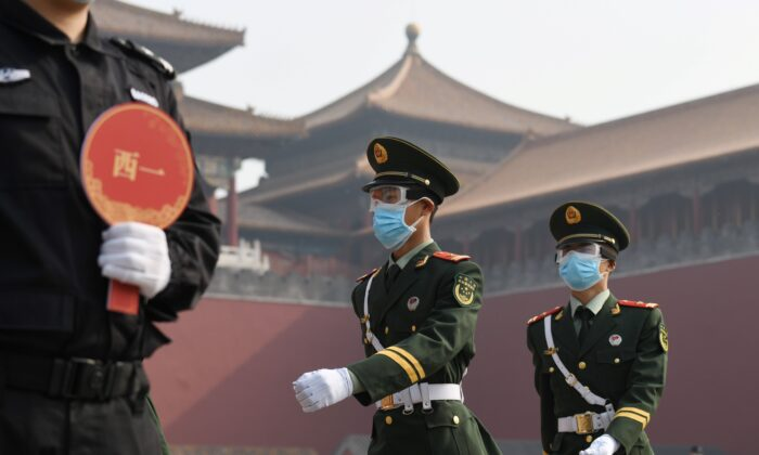 Paramilitary police officers wear face masks and goggles amid concerns of the COVID-19 CCP virus as they march outside the Forbidden City, the former palace of China's emperors, in Beijing, China, on May 1, 2020. (Greg Baker/AFP/Getty Images)