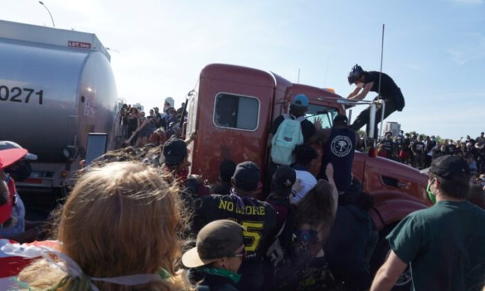 Protesters scale a truck that was driven onto a freeway with thousands of people on it in Minneapolis, Minn., on May 31, 2020. (Go Nakamura/Reuters)