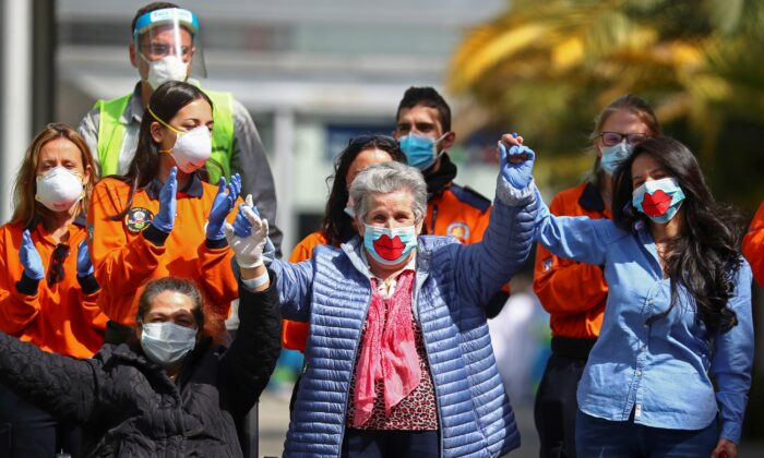 The final patients, Maria, Patrocina, and Miriam react after being discharged from a temporary hospital set up at IFEMA fairgrounds, before it's closure, amid the CCP virus outbreak in Madrid, Spain on May 1, 2020. (Sergio Perez/Reuters)