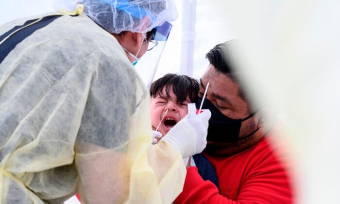 Jose Vatres (R) holds his son Aidin, who reacts as nurse practitioner Alexander Panis (L) takes a nasal swab sample to test for COVID-19 at a mobile testing station in a public school parking area in Compton, Calif., on April 28, 2020. (Robyn Beck/AFP via Getty Images)