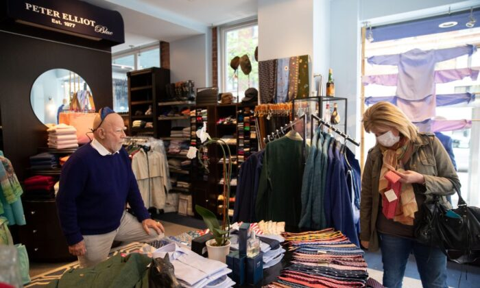 A customer shops at Peter Elliot boutique in New York City on April 29, 2020. Eliot Rabin, the owner of the boutique (L) is keeping his store open because he objects to the state order deeming his business non-essential, and says he has received widespread support for his stance. (Jeenah Moon/Getty Images)