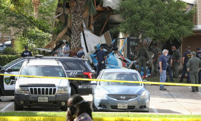 Authorities investigate the scene of a helicopter crash at an apartment complex in Houston on May 2, 2020. (Jon Shapley/Houston Chronicle via AP)