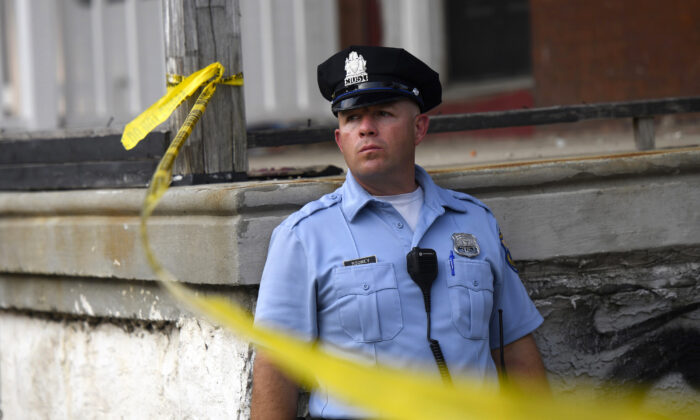 A police officer monitors activity near a residence while responding to a shooting in Philadelphia, Penn., in a file photo. (Mark Makela/Getty Images)