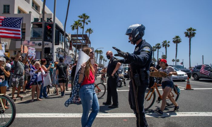 A police officer talks to a protestor at a demonstration in Huntington Beach, California on May 1, 2020. (Apu Gomes/Getty Images)