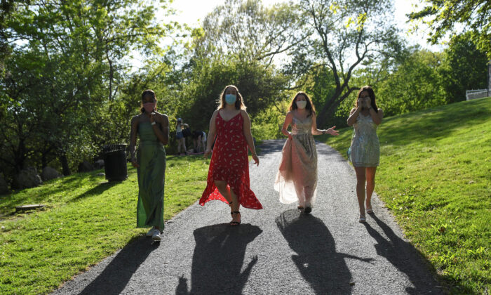 Mila Contreras-Godfrey, Katie Reisig, Gwyn McLear and Melina Bertsekas, high school seniors graduating from Beaver Country Day School, walk through Larz Anderson Park while posing for photographs in their prom dresses, in Brookline, Mass., May 22, 2020. (REUTERS/Faith Ninivaggi)