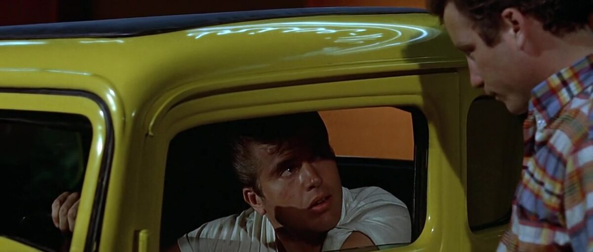 "boy in yellow car talks to boy outside car in ""American Graffiti"""