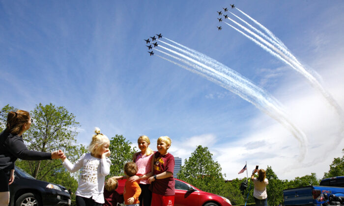 """The Ferry family, from Chantilly, Va., who were in the middle of taking a family photograph, are surprised by a second fly over by the Blue Angels and Thunderbirds, in a """"salute to frontline COVID-19 responders,"""" as seen near the U.S. Marine Corps War Memorial that depicts a flag raising over Iwo Jima, in Arlington, Va., on May 2, 2020. (Jacquelyn Martin/AP Photo)"""